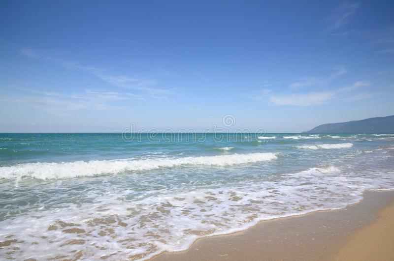 Turquoise tropical sea surf, wave foam, blue sky on empty sandy beach, Na Dan Beach in Nakhon Si Thammarat province of Thailand. Turquoise tropical sea surf royalty free stock image