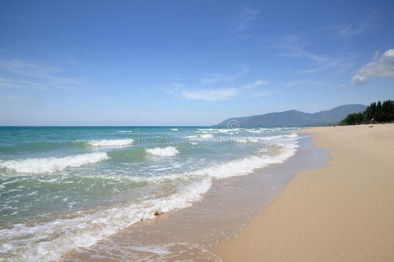 Turquoise tropical sea surf, wave foam, blue sky on empty sandy beach, Na Dan Beach in Nakhon Si Thammarat province of Thailand. Turquoise tropical sea surf royalty free stock photos