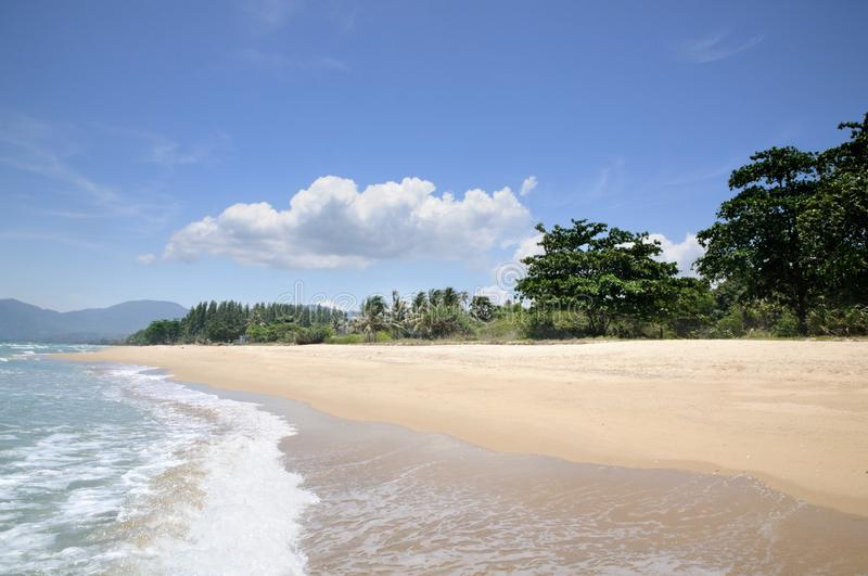 Turquoise tropical sea surf, wave foam, blue sky on empty sandy beach, Na Dan Beach in Nakhon Si Thammarat province of Thailand. Turquoise tropical sea surf stock photography