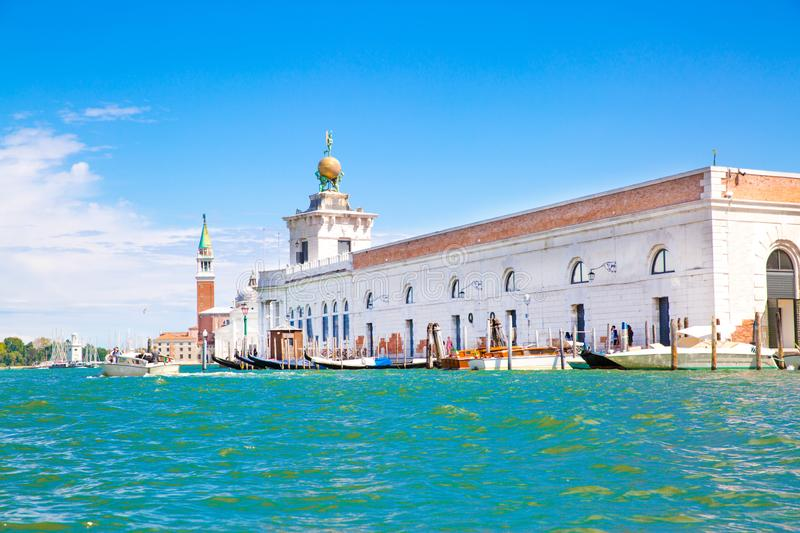 Turquoise water of Grand Canal in Venice, Italy. Old historical buildings. Campanile tower. On the background stock photography