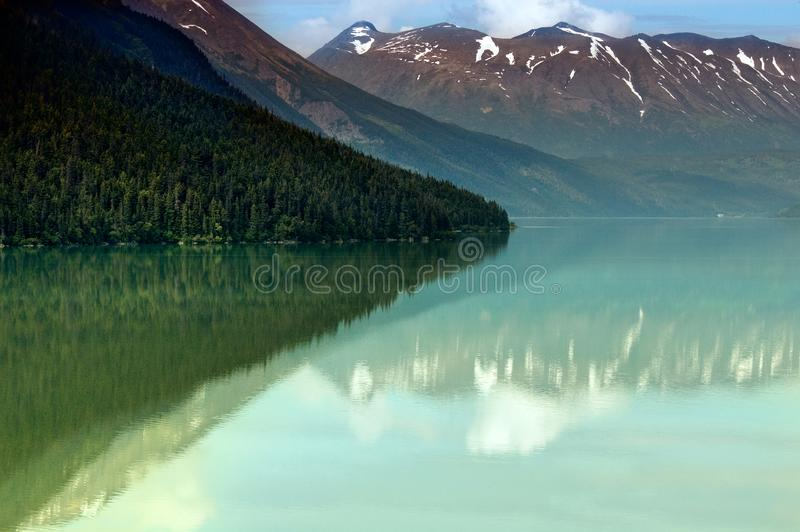 Kenai Lake, Alaska, turquoise water and mountains. The turquoise water of Kenai Lake turquoise water surrounded by snowcapped mountains in Alaska royalty free stock photo