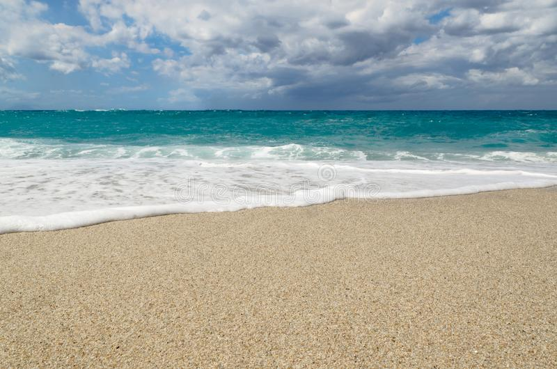 Turquoise water on the Riaci beach near Tropea, Italy. Turquoise water under cloudy sky on the Riaci beach. Located near Tropea, Italy royalty free stock photos