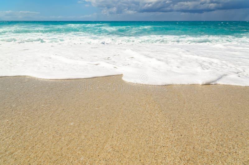 Turquoise water on the Riaci beach near Tropea, Italy. Waves under cloudy sky on the Riaci beach near Tropea, Italy royalty free stock photography