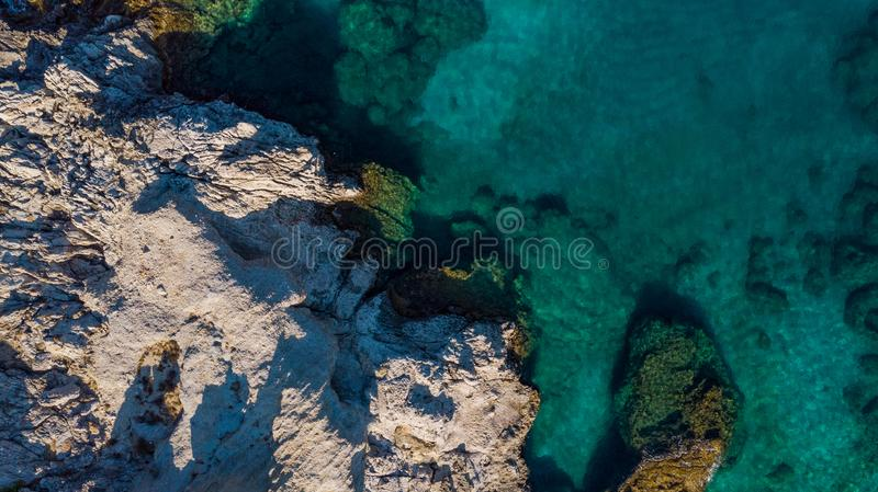 Turquoise Water and Rocky Shore on Greek Island, Aerial top Down View stock photos