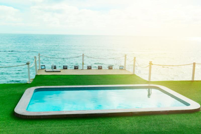 Swimming pool by the sea ,summer vacation and luxury living concept. Turquoise water of the  swimming pool by the sea ,summer vacation and luxury living concept royalty free stock photos