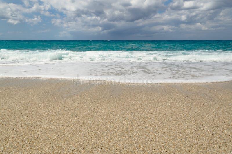 Turquoise water on the Riaci beach near Tropea, Italy. Turquoise water under cloudy sky on the Riaci beach near Tropea, Italy stock photos