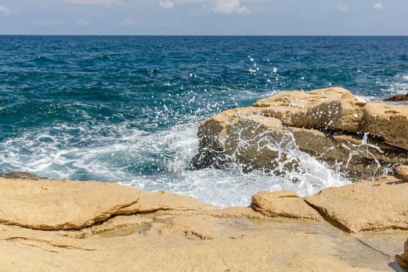 Turquoise wave breaks on rocks of the Sliema coast, Malta royalty free stock photos