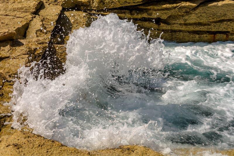 Turquoise wave breaks on rocks of the Sliema coast, Malta royalty free stock images