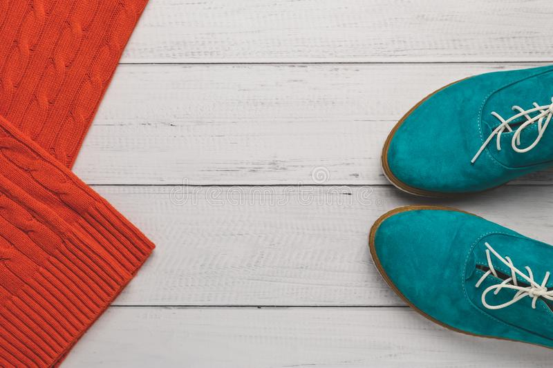 Turquoise women lace-up shoes and bright orange knitted sweater on light wooden background. Fashion concept, top view. Casual life royalty free stock photography