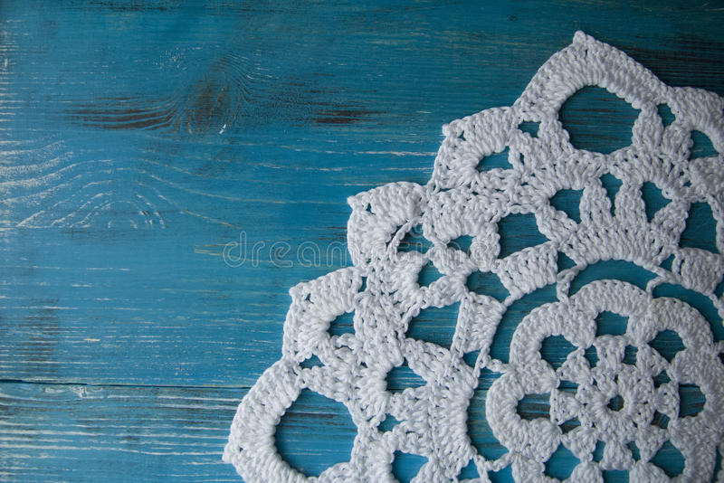 Turquoise wooden background in country style with crocheted lace doily stock images