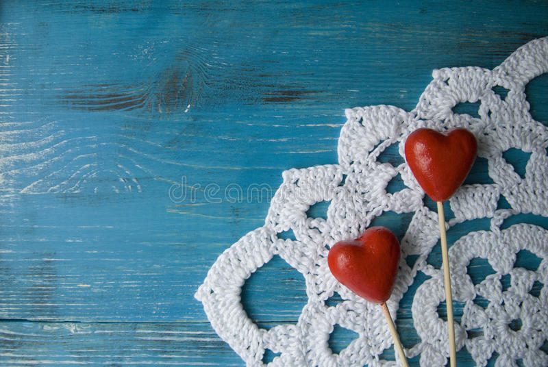 Turquoise wooden background in country style with two red hearts on crocheted lace doily stock photos