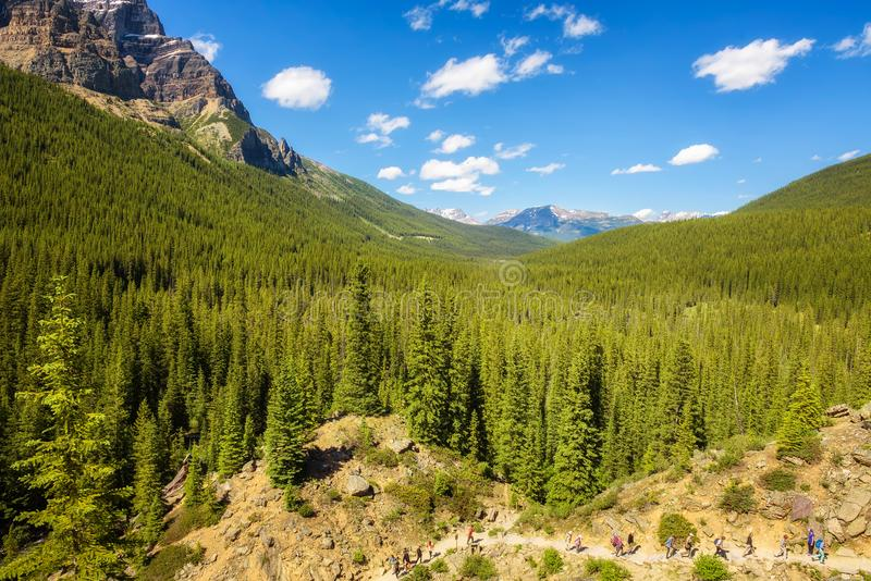 Turyści chodzi w kierunku Morena jeziora w kanadyjskich Skalistych górach obraz stock