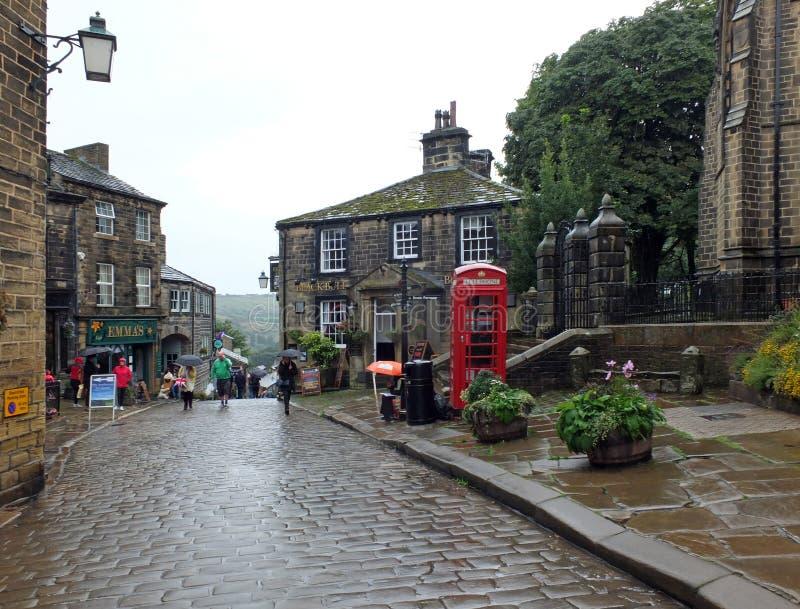 Turyści chodzi z parasolami na deszczowym dniu w centrum Howarth w zachodzie - Yorkshire historyczna wioska sławna dla bronte zdjęcie royalty free