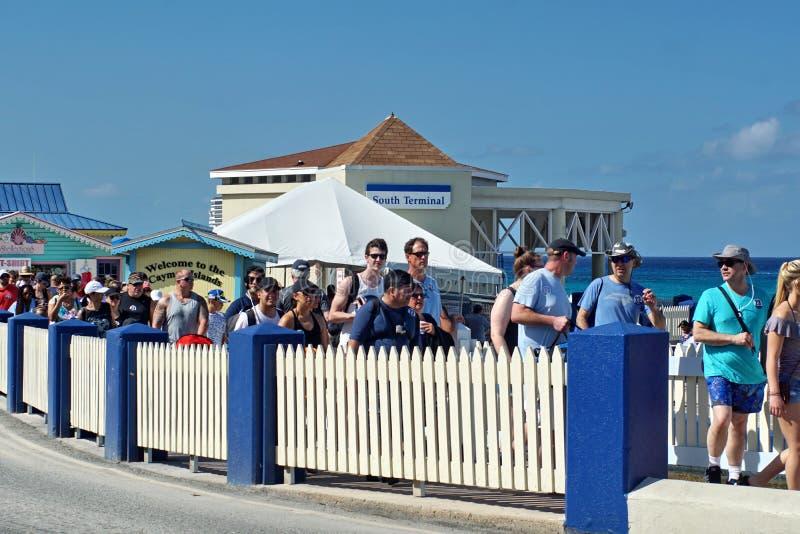 Turyści chodzi z powrotem statek wycieczkowy na Uroczystym kajmanie obraz royalty free