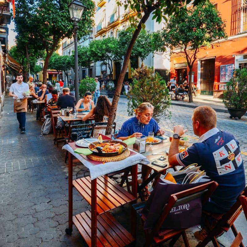 Turyści cieszą się przy restauracja tarasu typowo Hiszpańską kuchnią, owoce morza paella z kałamarnicami, mussels, milczkami i kr zdjęcie royalty free