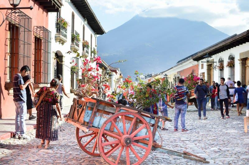 Turyści i miejscowi spacerują brukującego kamienia ulicy piękny kolonialny miasto Antigua na słonecznym dniu w Gwatemala, obraz stock