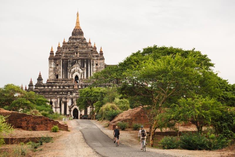 Turyści jedzie rowerowe pobliskie antyczne pagody w Bagan zdjęcia royalty free