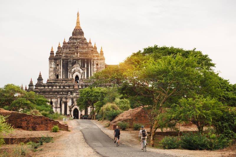Turyści jedzie rowerowe pobliskie pagody w Bagan na zmierzchu fotografia royalty free