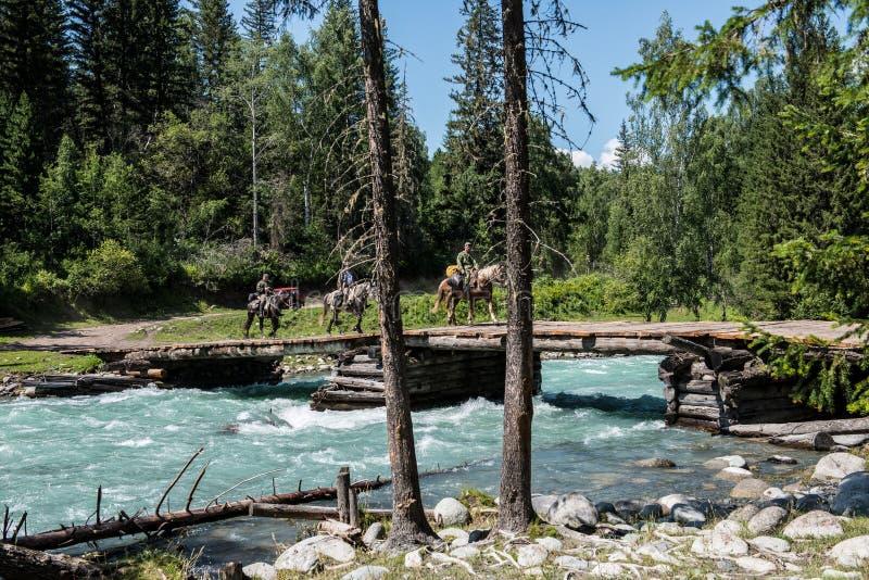 Turyści na horseback krzyżują halną rzekę na moscie zdjęcia stock