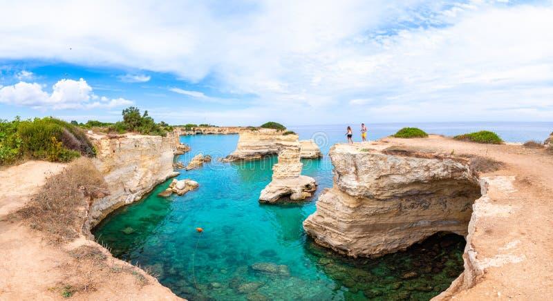 Turyści na krawędzi skały Plaża Torre Sant Andrea z miękkimi wapiennymi skałami i klifami, stosami morskimi, małymi zatokami i fotografia royalty free