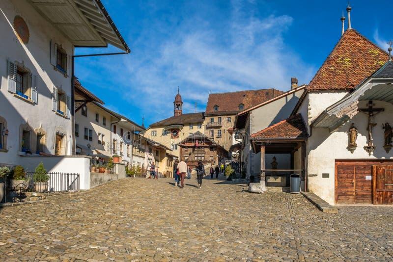 Turyści na starej średniowiecznej drodze w Gruyeres, Szwajcaria, w jesieni świetle obraz royalty free