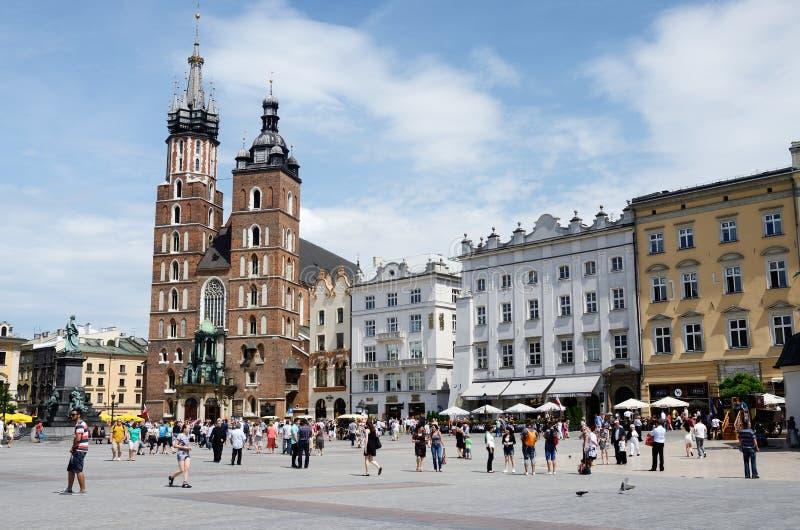 Turyści odwiedza głównego targowego kwadrat przed St. Mary bazyliką w Krakow, Polska zdjęcia stock