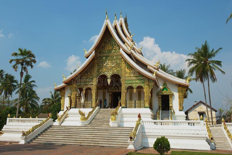 Turyści odwiedzają Buddyjską świątynię przy Haw Kham Royal Palace kompleksem w Luang Prabang, Laos obraz royalty free