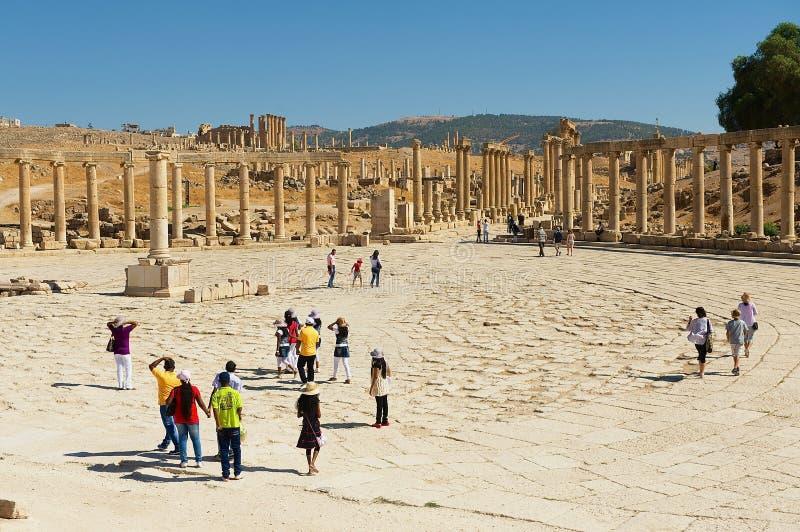 Turyści odwiedzają ruiny forum kolumnady i placu Owalna ulica w Jerash, Jordania obraz royalty free