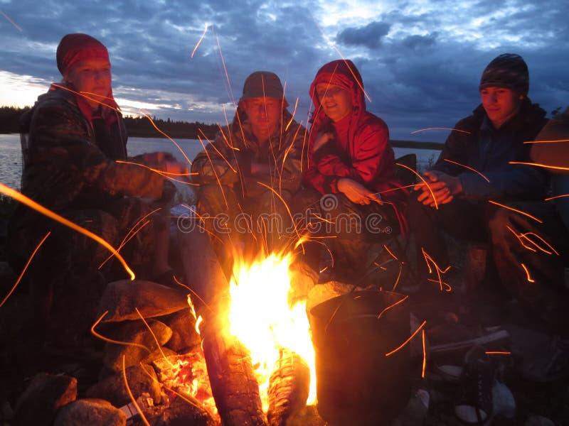Turyści ogrzewają przy ogieniem przy nocą zdjęcie stock