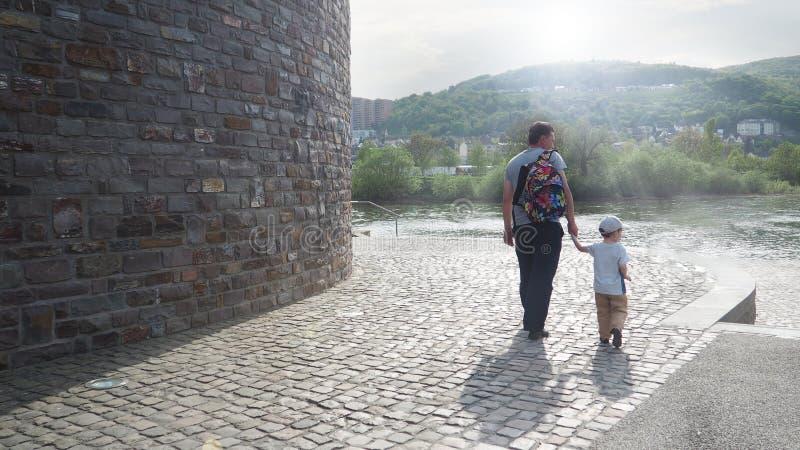 Turyści, ojciec i syn wpólnie chodzi wzdłuż rzecznego bulwaru, obrazy royalty free
