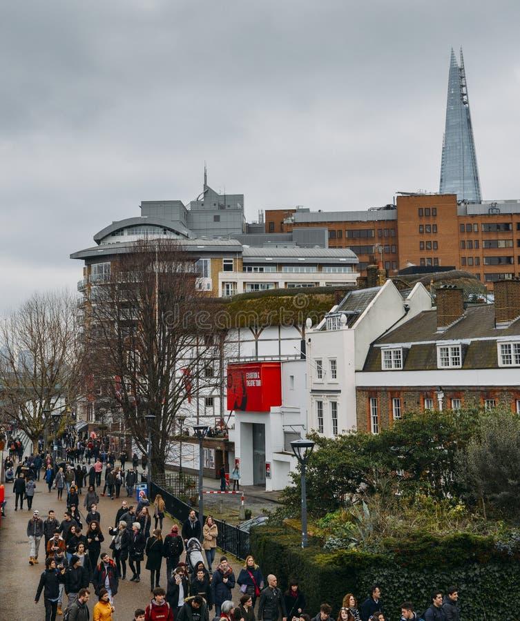 Turyści przy Jubileuszowym spacerem na Południowym banku Rzeczny Thames z Szekspir ` s kulą ziemską, replika oryginalny 1599 obraz stock