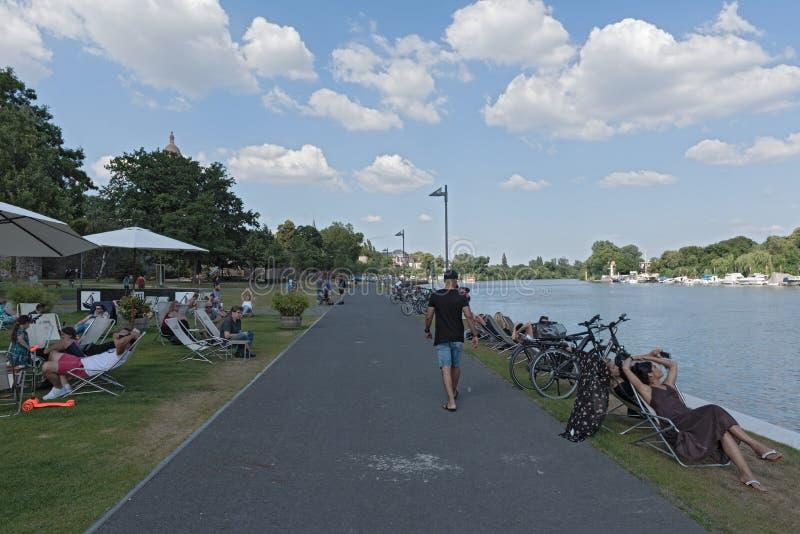 Turyści w holów krzesłach na nabrzeżu na głównej rzece w Frankfurt Hoechst, Germany fotografia stock