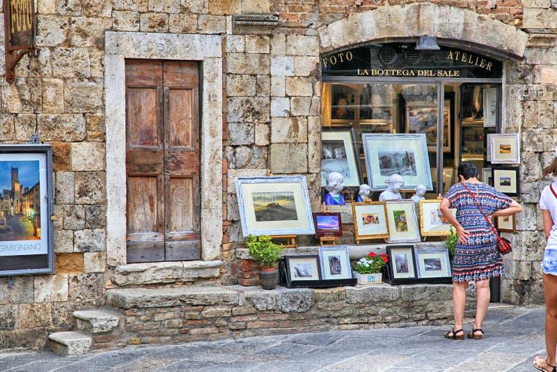 Turyści w prezenta sklepie przy średniowiecznym miasteczkiem San Gimignano, fotografia stock