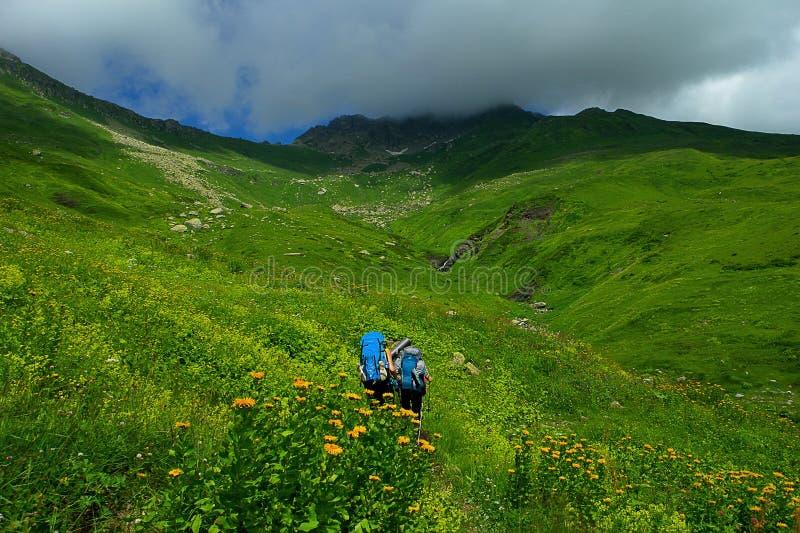 Turyści z wielkimi plecakami są podróżni w górach na pojęciu stylu życia sporta wspinaczkowy tło zdjęcie royalty free