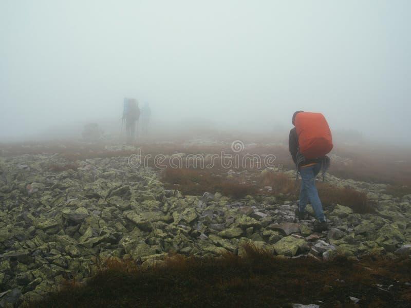 Turystów podróżnicy chodzi przez skał w gęstej mgle mleko z plecakami fotografia stock