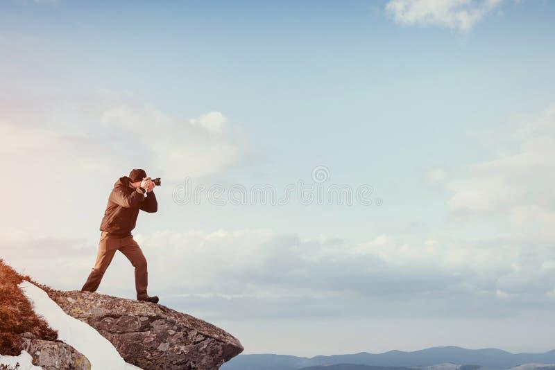 Turystów spojrzenia przy krajobrazem Fotograf na górze góry fotografia stock