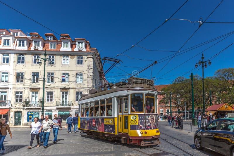 Turysta i miejscowi jedzie tradycyjnego żółtego tramwaj w w centrum Lisbon w pięknym niebieskim niebie, Lisbon, Portugalia, Maj - zdjęcia stock
