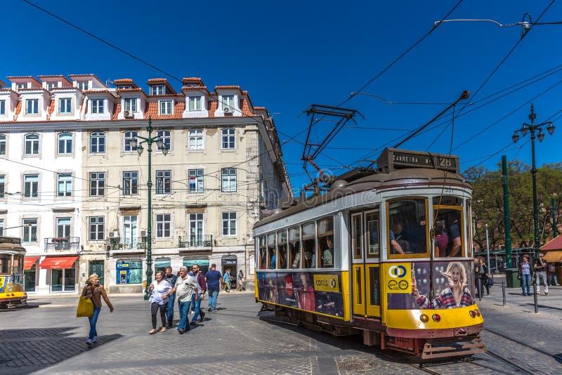 Turysta i miejscowi jedzie tradycyjnego żółtego tramwaj w w centrum Lisbon w pięknym niebieskim niebie, Lisbon, Portugalia, Maj - obrazy royalty free