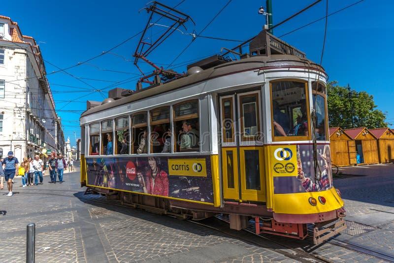 Turysta i miejscowi jedzie tradycyjnego żółtego tramwaj w w centrum Lisbon w pięknym niebieskim niebie, Lisbon, Portugalia, Maj - zdjęcie stock