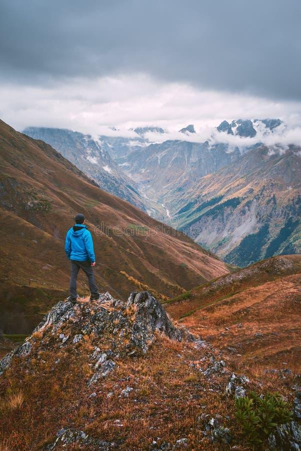 Turysta w niebieskiej marynarki pozyci na skale w górach fotografia stock