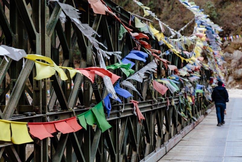 Turysta z łzy kolorową Tybetańską modlitwą zaznacza falowanie i swaddled z mostem nad zamarzniętą rzeką przy doliną Thangu i Chop obraz royalty free