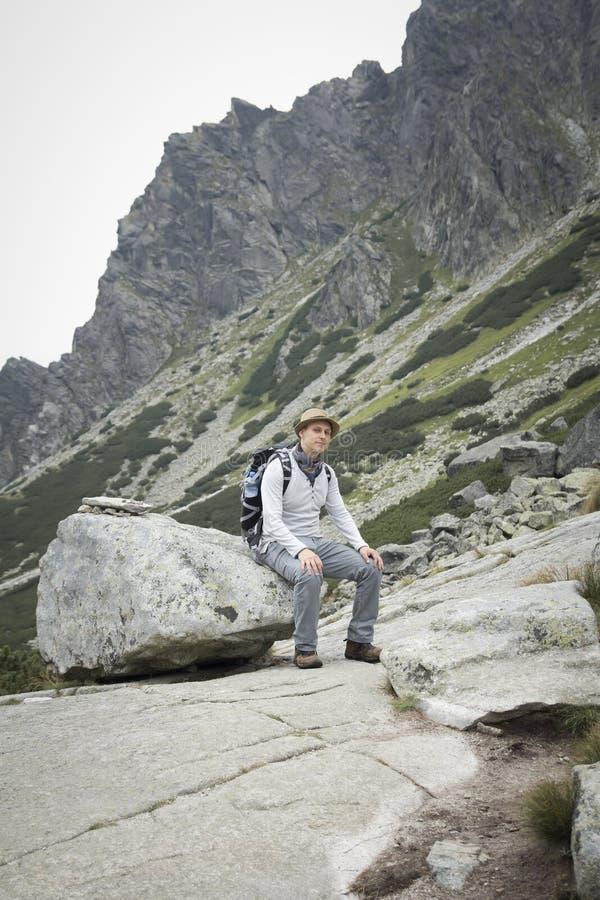 Turysta z plecaka obsiadaniem na głazie w górach fotografia royalty free