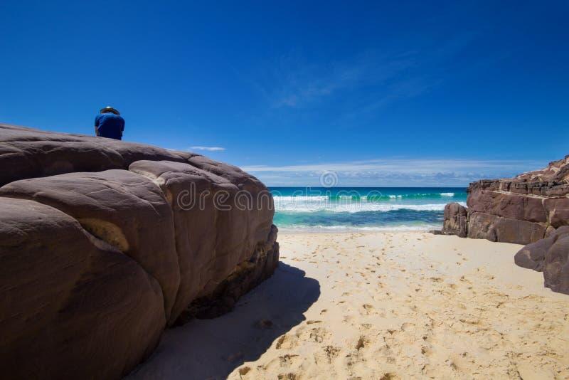 Turysta z plecakami na ampuła kamiennym i cieszy się Dennym widoku. Ben Boyd park narodowy, Australia obrazy royalty free