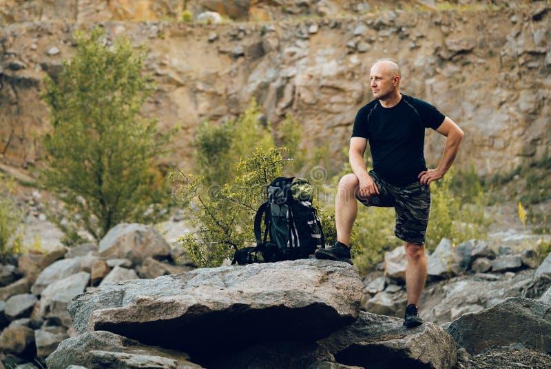 Turysta z plecakiem stoi na skale i pozuje dla fotografii Podróżnik imponuje krajobrazem zdjęcia stock