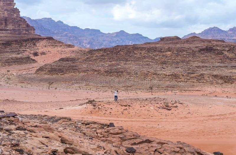 Turysty stojaki na wzgórzu i biorą wadiego rumu pustyni fotografię na jego telefonie komórkowym blisko Aqaba miasta w Jordania zdjęcie royalty free