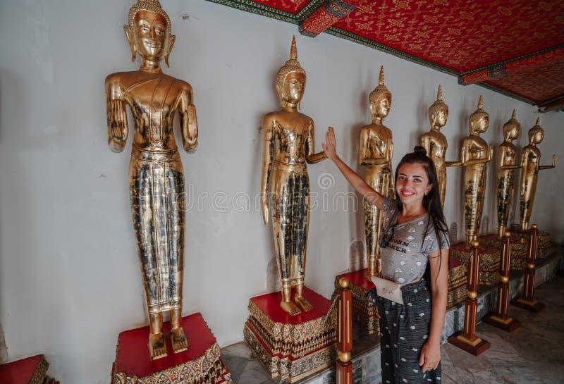 turysty wakacje Dziewczyna na wycieczce w antycznej ?wi?tyni Kobieta dotyka ?yczliwego gest statua obrazy royalty free