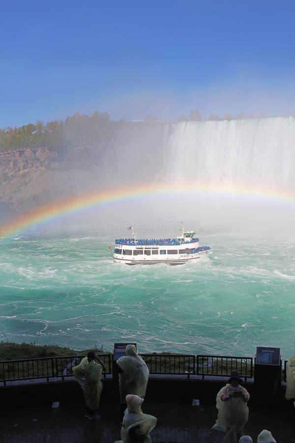 Turysty zegarka Niagara spadki objeżdżają łódź pod pełnym tęczy vert zdjęcie royalty free