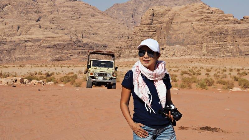 Turystyczna Azjatycka kobiety przewożenia kamera w wadiego rumu pustyni, Jordania z safari samochodem behind obraz stock