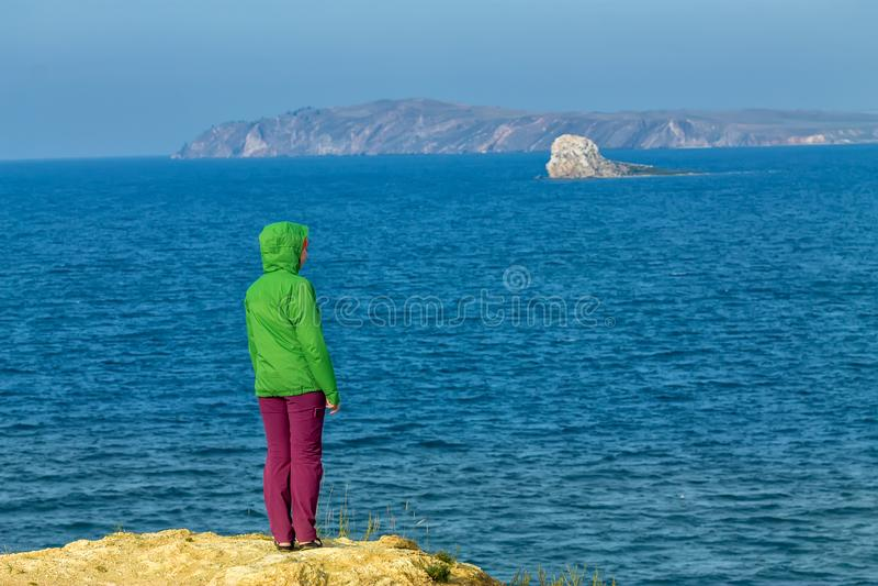Turystyczna dziewczyna przegapia góry i wodę chodzi w żółtej trawie przez pole obrazy royalty free