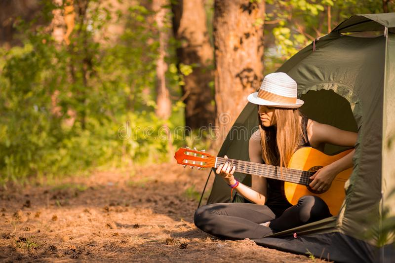 Turystyczna dziewczyna w kapeluszu siedzi w namiocie i bawi? si? gitary poj?cie Turystyka odpoczynek na naturze fotografia royalty free